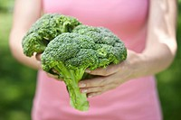 Woman holding bunch of broccoli