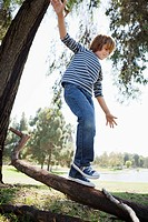 Boy balancing on log