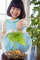 Girl feeding pet fish