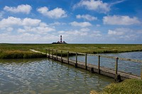 Footbridge on path leading to lighthouse, Westerhever, Germany