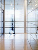 Businesswoman walking in a contemporary office hallway (thumbnail)