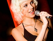Photo of pretty blonde with microphone holding it by her mouth