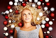 Creative image of lying blond girl with lots of decorative balls on ends of her hair