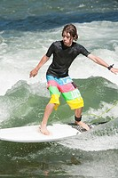 Teenage boy surfing on river, Munich, Bavaria, Germany