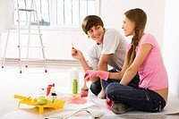 Photo of young couple sitting on floor of new flat and interacting