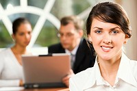 Portrait of smiling brunette Caucasian woman and two talking businesspeople on the background working on the laptop