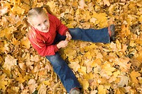 Above view of smiling girl sitting on autumnal ground and looking at camera