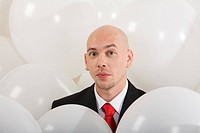 Image of handsome businessman inside white balloons