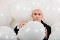 Photo of attractive male holding big white balloon in hands and looking at camera
