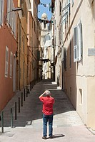 Man photographing old apartment buildings, Bastia, Corsica