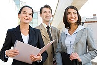 Portrait of business team outside looking straight and slightly upwards with smiles