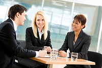 Portrait of friendly business team sitting around table and communicating in office