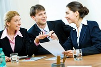 Portrait of three white_collar workers sitting at table and working with documents in the office