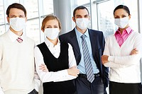 Portrait of business team in protective masks looking at camera