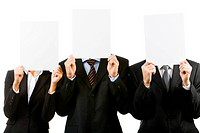 Row of three business partners hiding their faces behind blank papers