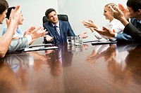 Photo of happy business partners applauding to confident leader at meeting
