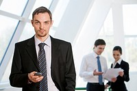 Portrait of serious businessman looking at camera with cell in hand on background of interacting co_workers