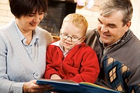 Portrait of attentive boy looking at page of book while reading it with his grandparents