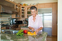 Senior woman chopping peppers in kitchen