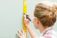 Woman measuring plywood and marking with pencil