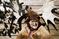 Boy dressed up as bear in front of moose antlers