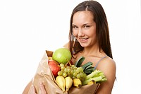 Portrait of pretty girl with big paper sack full of different fruits and vegetables isolated over white background