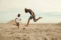 Boys playing football on beach