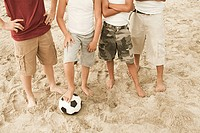 Boys standing on beach with football