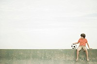 Boy sitting on wall with football