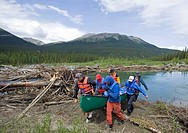 Men portaging, carrying a canoe over land, bypassing obstacle, log jam behind, upper Liard River, Yukon Territory, Kanada