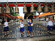 Children striking a bell, Thailand, Asia