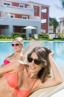 Two women sunbathing on sunloungers at poolside