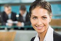 Close_up of beautiful woman smiling on the background of two businesspeople in a room