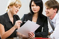 Successful manager is holding a document and showing it to her colleagues in the office