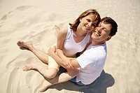 Portrait of amorous couple embracing while sitting on sand