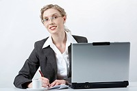 Image of young successful employer writing and looking at camera at workplace