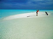 Man playing golf on isolated sandbar                                                                                                                  ...