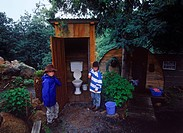 Tasmania, children standing near outhouse toilet                                                                                                      ...