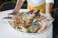 Cook with seafood platter at the beach restaurant Foresta, Marina di Pisa, Tuscany, Italy, Europe