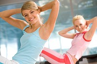 Photo of cheerful girl doing exercise in sport gym with another woman at background