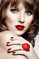 Portrait of a young woman wearing a ring made from a strawberry with a seductive look, jewellery