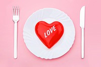 Image red heart on plate with spoon and fork near by