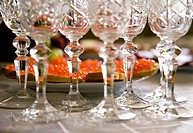 Close_up of crystal glasses necks on wedding table with tasty sandwiches at background
