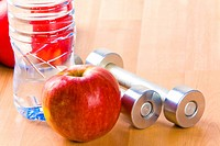 Photo of big red apple with two barbells and bottle of water near by on wooden surface