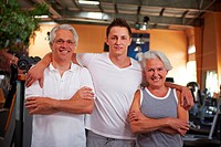 Old couple with personal fitness trainer in the gym