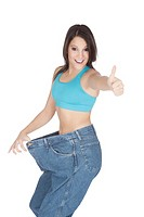 Woman showing weight loss by wearing an old pair of jeans