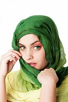 Portrait of shy mysterious beautiful Caucasian Hispanic Latina woman face with green penetrating eyes and green fashion scarf wrapped around head, iso...