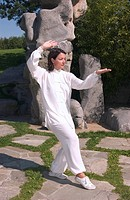 Woman, early 40s, doing Tai Chi in a Chinese garden in Berlin, Germany, Europe