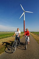 Cyclists in front of wind turbines, Sexbierum, Friesia, Holland, Netherlands, Europe