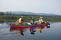 Family with young boy in a canoe, paddling, canoeing, calm Teslin River, reflections, Yukon Territory, Canada